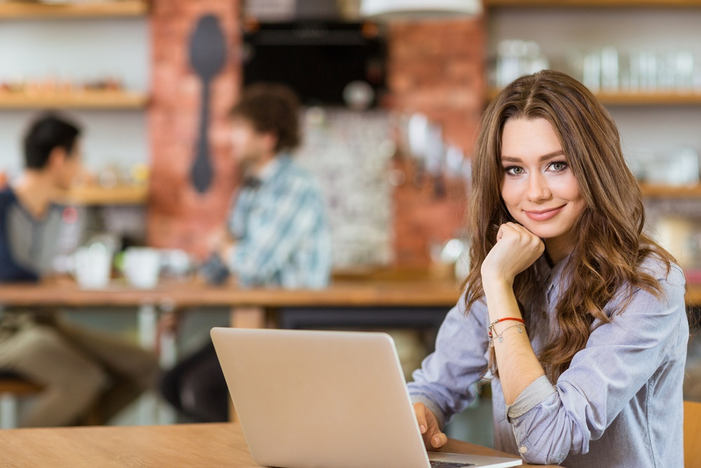 Attractive positive young curly female in grey shirt using laptop in cafe