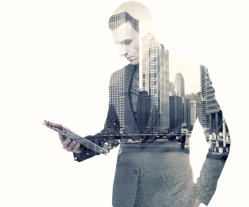 Double exposure of a businessman and a city using a tablet over white background.jpeg